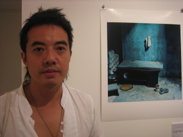 Dinu Li standing next to his artwork