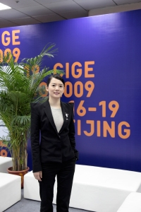 Wang Yi Han, CEO of CAE Media(Beijing Chinese Art Exposition's Media Co., Ltd), standing in front of the banner for the 2009 CIGE(China International Gallery Exposition Exhibition) in Beijing